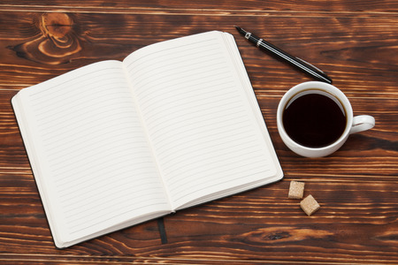 空白メモ帳を開きます。一杯のコーヒー。木製の背景。 写真素材