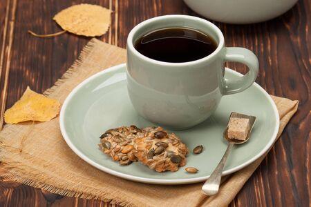 Herfst concept. Kopje thee of koffie. Cookies met zaden. Houten achtergrond.
