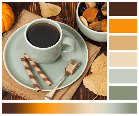 autumn colour: Autumn Concept. Cup Of Tea Or Coffee. Dried Fruits. Chocolate Sweets. Wooden Background. Palette With Complimentary Colour Swatches.