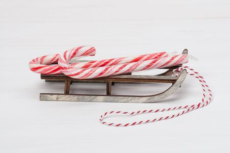 painted wood: Christmas Candy Cane On Wooden Sledge. White Painted Wood Background. Stock Photo
