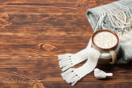 taza cafe: Mug Of Hot Chocolate Or Coffee With Marshmallows. Natural Wool Scarf. Wooden Background With Copy Space.