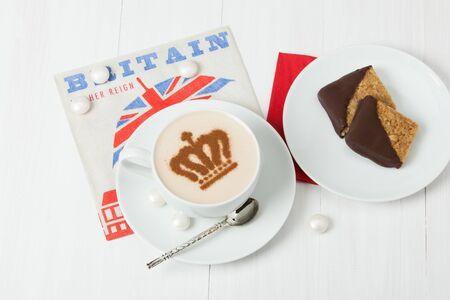 servilleta: Caf� decorado con corona de la reina. British s�mbolo servilleta de papel. Dulces. Mesa de madera blanca. Foto de archivo