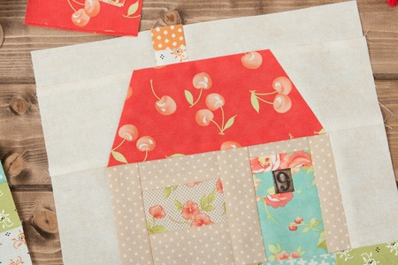 quilted: Quilted House. Sewing And Quilting Accessories. Fabric Patches On Wooden Table