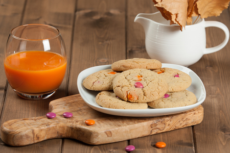 Homebaked Chewable Butter Biscuits With Colored Chocolate Sweets. Carrot Juice. Olive Tree Board. Autumn Leaves