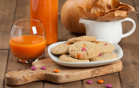 Homebaked Chewable Butter Biscuits With Colored Chocolate Sweets. Carrot Juice. Olive Tree Board. Autumn Leaves. Pumpkins