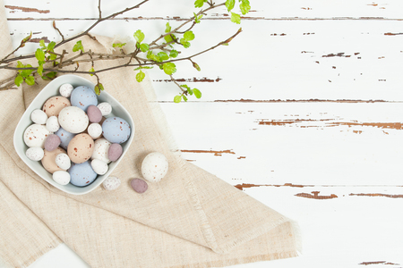 beige: Chocolate Easter Eggs. Natural Linen Textile. Green Spring Leaves. White Wooden Scratched Background Stock Photo