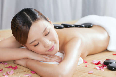 A young lady enjoying stone massage at spa  photo