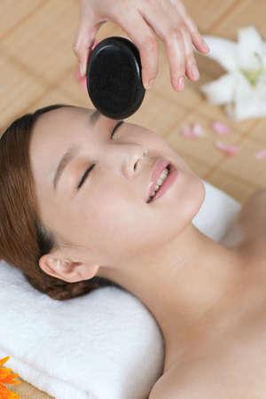 A young lady enjoying stone massage at spa  photo