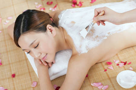A young lady enjoy body mask in spa salon  photo