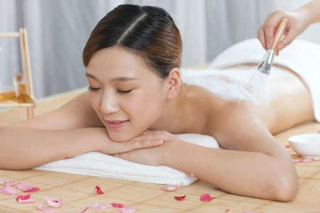 A young lady enjoy body mask in spa salon  photo
