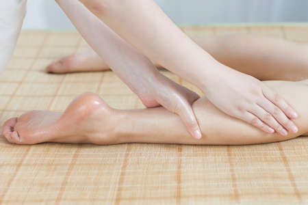 Foot massage for young lady in spa salon  photo
