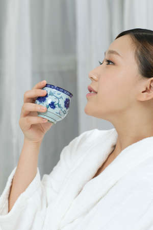 A young woman with a bathrobe enjoying tea  photo