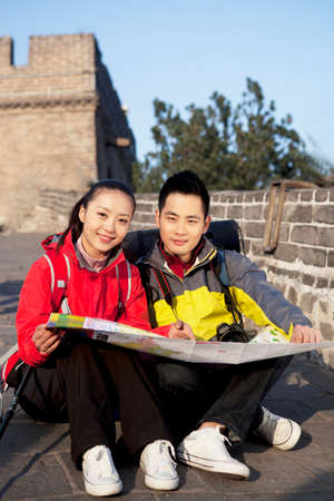 A young woman use the mobile phone in the Great Wall