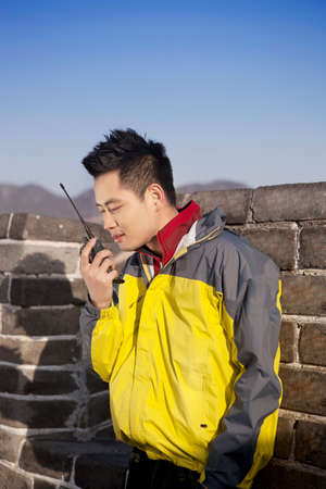 Young man using walkies talkie in the Great Wall
