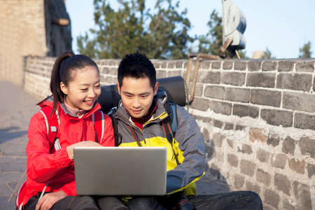 A young woman using laptop in the Great Wall