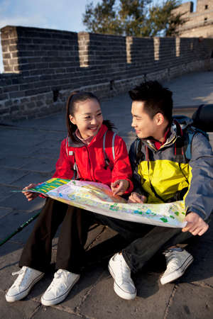 A young couples using tourism map at great wall