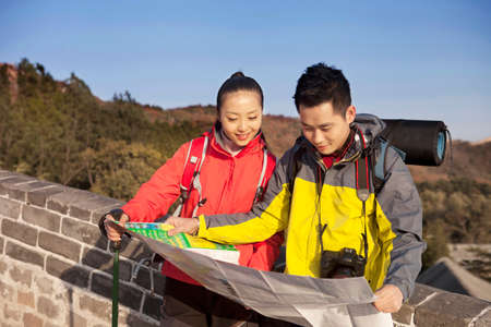Young couples in the Great Wall looking at map