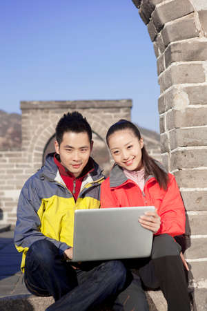 Young couples in the Great Wall using laptop