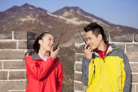 Young couples in the Great Wall using walkies talkie