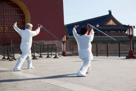 Two old folks dancing swords in the park
