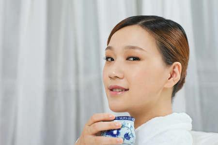 A young woman wearing a bathrobe drinking tea