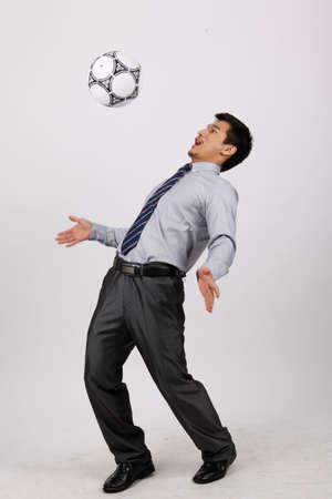 A business man playing football Фото со стока