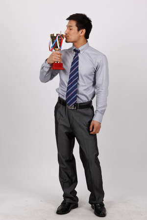 A business man holding a trophy