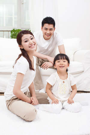 Young family sitting in couch Banco de Imagens