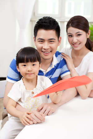 Family of three playing paper airplane