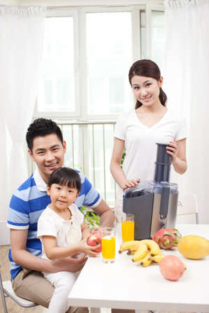Happy family making juice with electric juicer