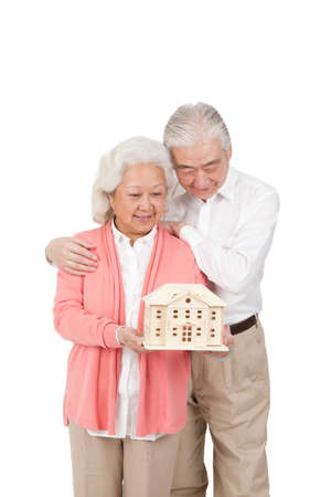 Senior couple holding building model