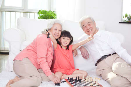 Senior couple with granddaughter playing game of go