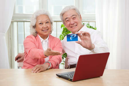 Senior couple holding credit card