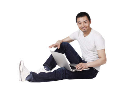 Cheerful businessman using a laptop on carpet