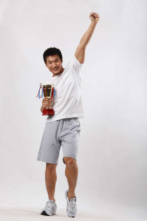 A young man in casual wear holding a trophy