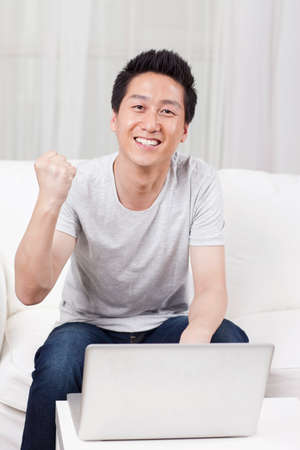 Cheerful businessman using a laptop in sofa