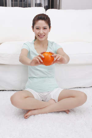 Young woman holding orange beside a couch