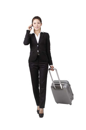 Businesswoman using cell phone,pulling suitcase Archivio Fotografico