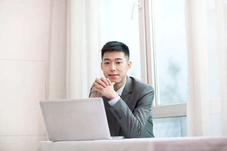 Portrait of a young businessman sitting in the front of the laptop