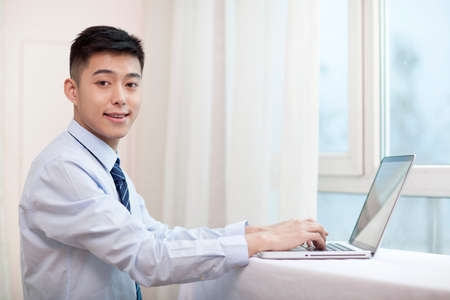 Portrait of a young businessman using a laptop