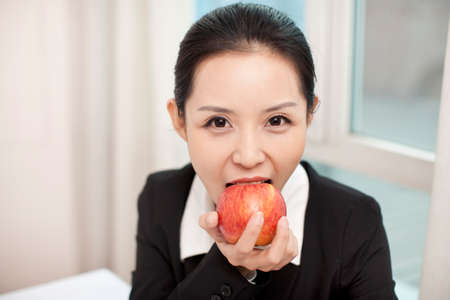 Businesswoman in her office eating an red apple