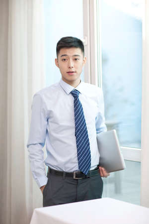 Portrait of a young businessman using the laptop Stockfoto
