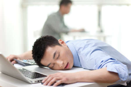 Portrait of young businessman sleeping on laptop by desk 免版税图像