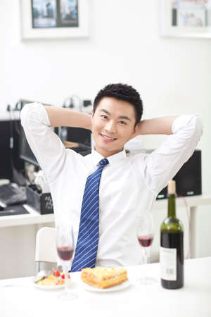 Portrait of businessman sitting at desk with food