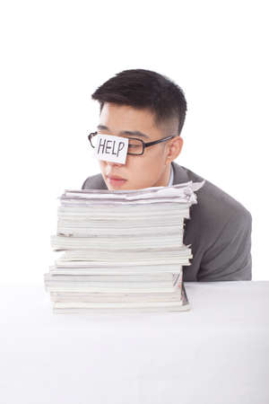 Portrait of a young businessman leaning on a stack of files