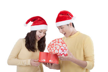 Portrait of a young couple wearing Santa hats holding gifts