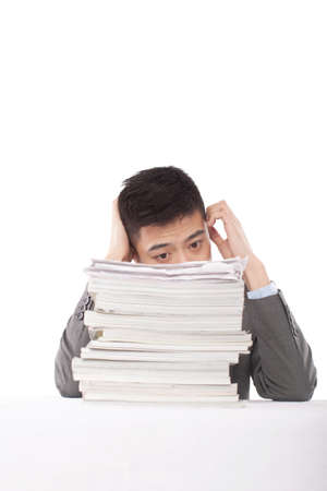 Portrait of a young man sitting on the desk with a stack of files, portrait Imagens