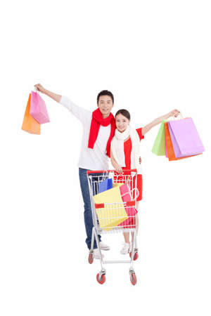 Portrait of young couple pushing a shopping cart, with shopping bags, opening arms