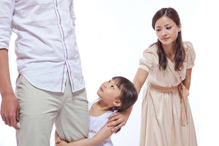 Girl clinching father's leg, mother pulling at daughter's shoulder