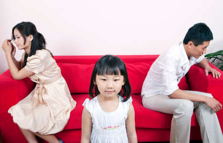 Girls standing, her hostile parents sitting on the sofa